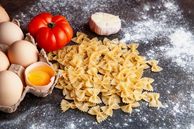 Quelques macaroni aux œufs, tomate et ail sur fond texturé foncé, vue de dessus.
