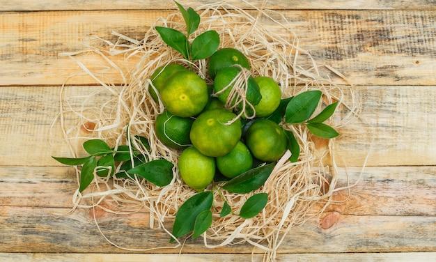 Quelques mandarines avec des feuilles sur planche de bois
