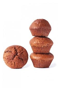 Quelques muffins à la pâte au chocolat noir sur isolé sur fond blanc.