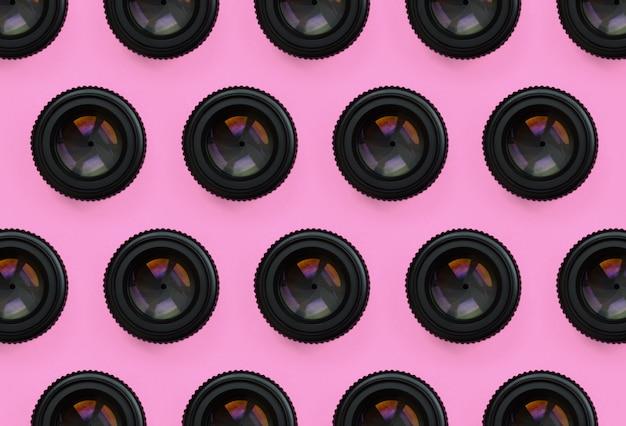 Quelques objectifs d'appareils photo à ouverture fermée reposent sur une texture rose pastel