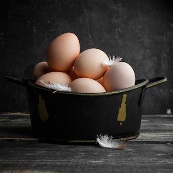 Quelques œufs avec des plumes dans un pot sur fond de bois foncé, vue latérale.