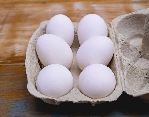 Quelques œufs de poule crus blancs dans un petit plateau sur une table en bois