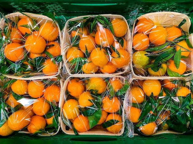 Quelques oranges dans des boîtes en plastique