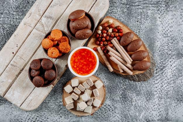 Quelques petits gâteaux avec des gaufres et de la gelée sur des assiettes et des bols sur une texture légère