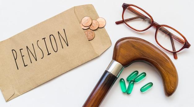 Quelques pièces de monnaie dans une enveloppe brune avec du personnel, des lunettes et des médicaments sur fond blanc