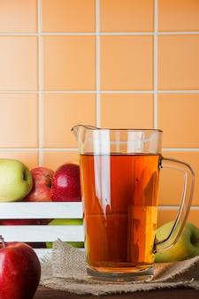 Quelques pommes fraîches avec du jus de pomme dans une boîte sur fond de carreaux orange, vue latérale. espace pour le texte
