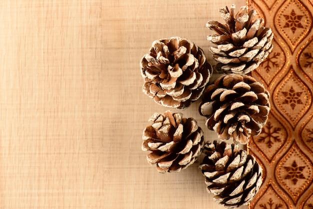 Quelques pommes de pin sur ruban marron décoratif et bois