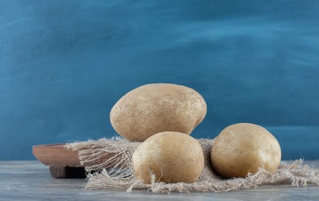 Quelques pommes de terre sur le dessous de plat, à bord sur la table de marbre.