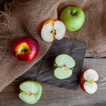 Quelques pommes vertes et rouges coupées en deux sur bois, tissu et fond en bois foncé, vue de dessus.