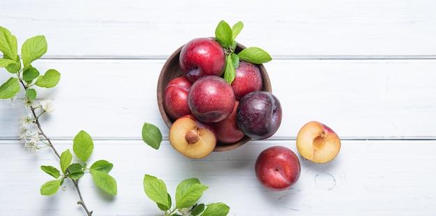 Quelques prunes rouges juteuses et sucrées dans un bol avec des feuilles vertes sur fond de bois blanc. orientation horizontale. vue de dessus et copie de l'image de l'espace