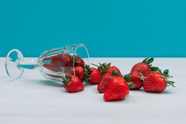 Quelques tas de fraises dans un verre sur fond bleu foncé, vue latérale.