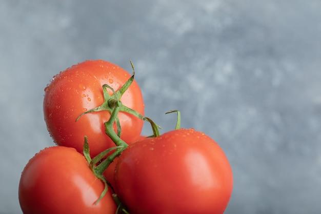 Quelques tomates juteuses sur gris.
