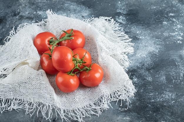 Quelques tomates juteuses sur un sac blanc.