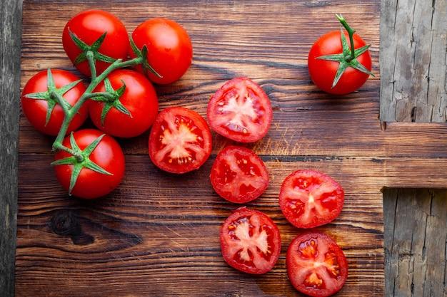 Quelques tomates et tranches avec couteau sur une vue de dessus de planche à découper en bois.
