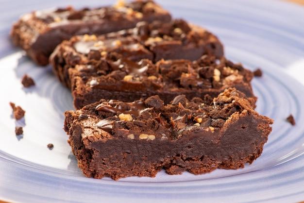Quelques tranches de brownie sur une assiette bleue.