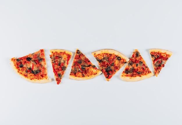 Quelques tranches de pizza sur fond de stuc bleu clair, vue de dessus.