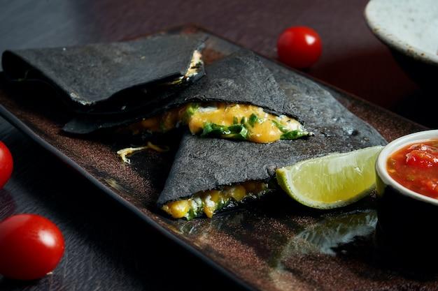 Quesadilla au four appétissante avec 4 types de fromage à la tortilla noire sur une plaque en céramique sur une table noire .. cuisine mexicaine moderne.