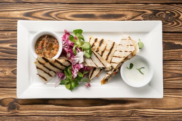 Quesadilla grillée avec filet de poulet avec salade et deux sauces différentes sur une plaque en céramique blanche