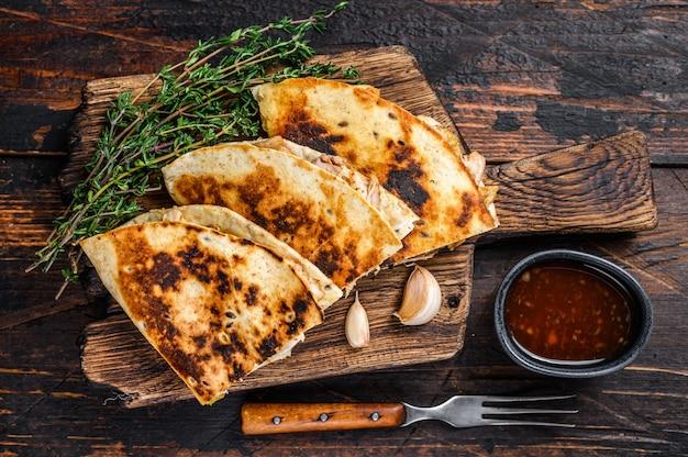 Quesadilla mexicaine au poulet, paprika, fromage et coriandre sur une planche à découper en bois.