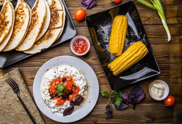 Quesadilla, salade au fromage blanc et aux tomates, deux maïs sur une table en bois.