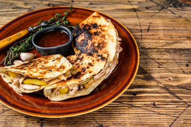 Quesadilla avec viande de poulet, paprika, fromage et coriandre sur une planche à découper.