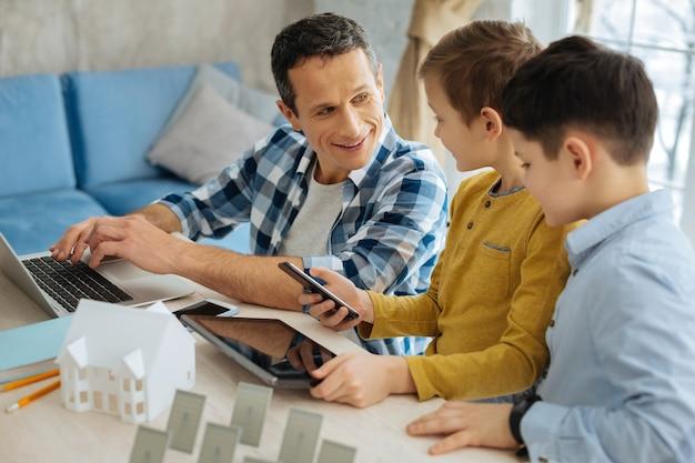 Des questions curieuses. garçons pré-adolescents optimistes tenant un téléphone et une tablette et posant des questions à leur père sur leur utilisation à son travail pendant que l'homme tapant sur l'ordinateur portable