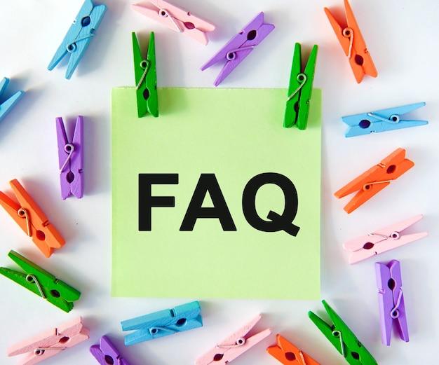 Les questions de la faq sont répondues sur un autocollant vert avec des pinces à linge multicolores
