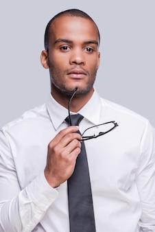 En quête d'inspiration. gentil jeune homme africain en chemise et cravate tenant des lunettes