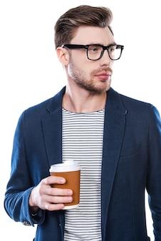 En quête d'inspiration. gentil jeune homme tenant une tasse de café et regardant loin en se tenant debout sur fond blanc