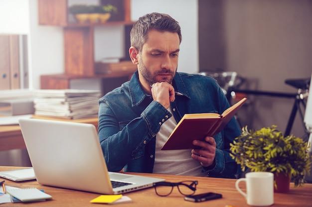 En quête d'inspiration. jeune homme réfléchi regardant son ordinateur portable alors qu'il était assis sur son lieu de travail au bureau