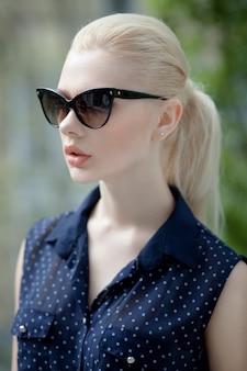 Queue de cheval et lunettes de soleil femme blonde