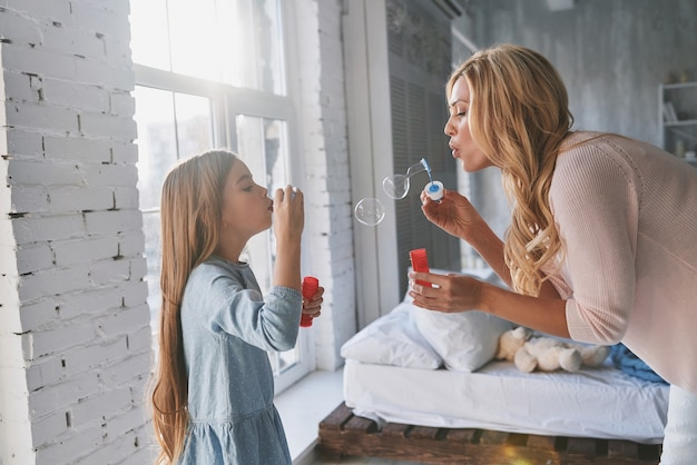 Qui est devenu plus gros ? mère et fille soufflant des bulles de savon tout en passant du temps à la maison