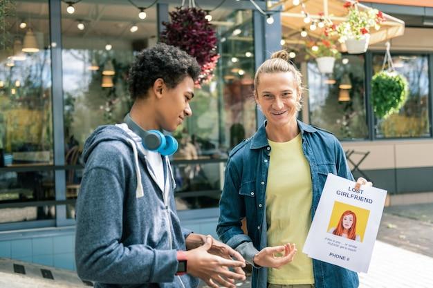 Qui est-ce. homme afro-américain positif regardant la publicité sans connaître la fille sur la photo