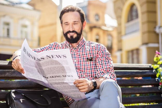 Ce qui est nouveau. homme barbu agréable reposant sur le banc en lisant un journal