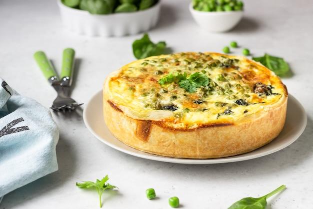Quiche aux épinards et aux pois verts, tarte ou tarte avec les ingrédients nécessaires pour la cuisson.