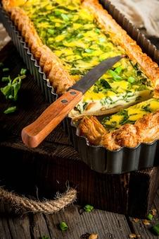 Quiche lorraine de pâte feuilletée, aux jeunes oignons verts et épinards sur vieille table rustique en bois.