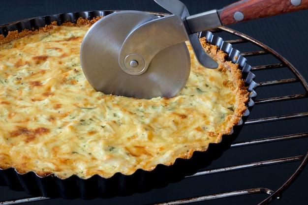 Quiche maison tranchée avec poulet, fromage et oignon vert et persil et couteau à pizza sur fond noir