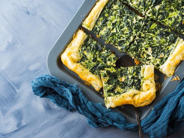 Quiche salée aux épinards avec fromage à la crème sur une plaque de cuisson