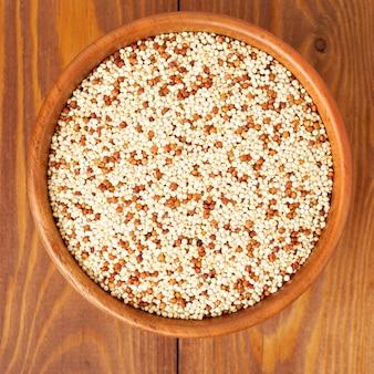 Quinoa cru dans un bol en bois, superaliment. fond en bois marron, vue de dessus.