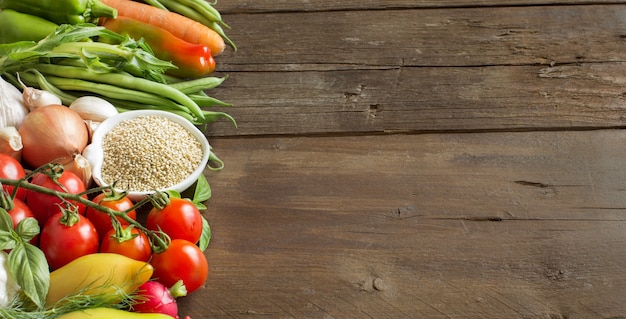 Quinoa dans un bol et légumes frais sur une table en bois