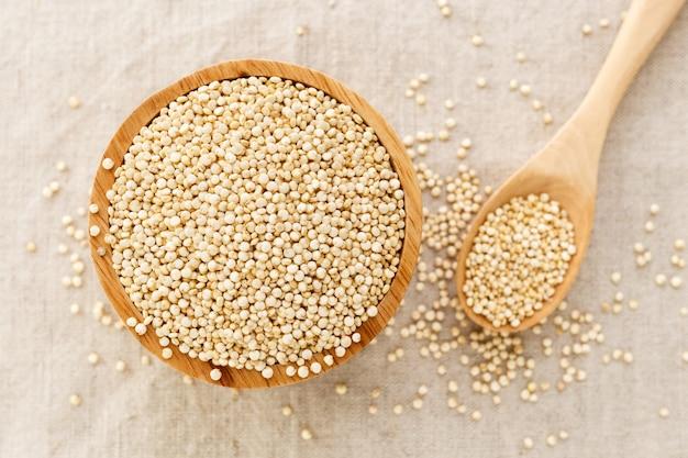 Quinoa dans une cuillère en bois et un bol