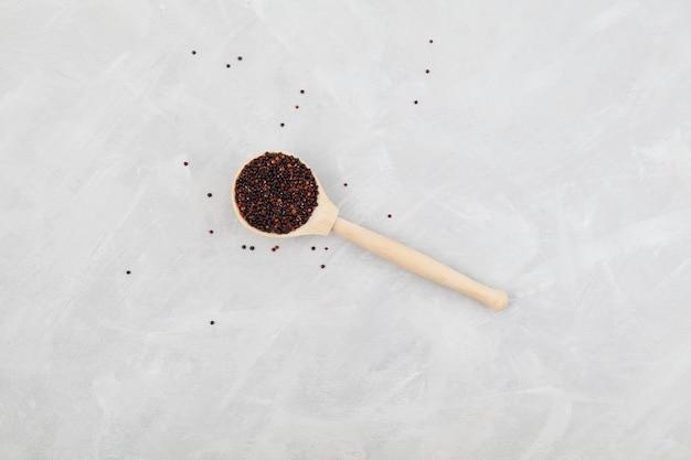 Quinoa noir biologique dans une cuillère en bois sur fond gris clair. vue de dessus, copiez l'espace.