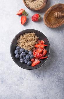 Quinoa salade diététique végétalienne saine avec myrtille, fraise, miel et graines de chia.