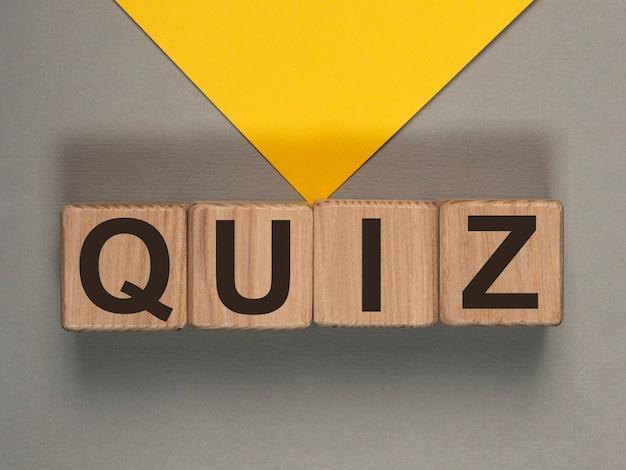 Quiz ou mot de concept de quiz sur des cubes en bois sur le fond gris et jaune