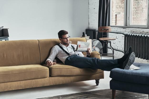 Quoi de neuf dans le monde ? jeune homme élégamment vêtu, lisant un journal et tenant un verre assis sur un canapé