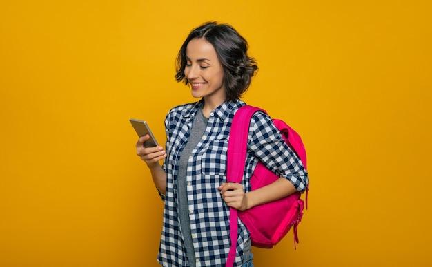 Quoi de neuf sur internet? une belle jeune étudiante, habillée avec désinvolture, avec son joli sac à dos rose sur une épaule, regardant avec un large sourire dans son smartphone.