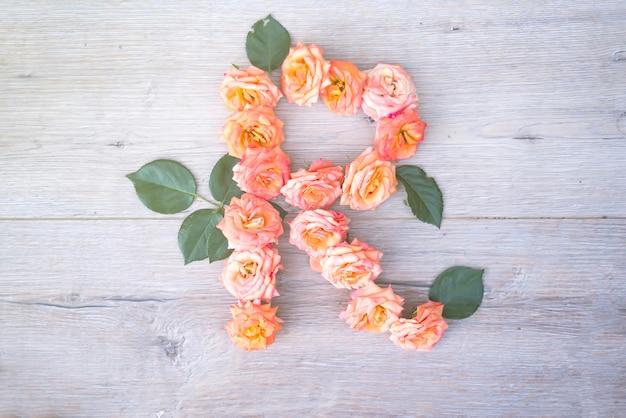 R, alphabet fleur de roses isolé sur fond en bois gris, plat poser