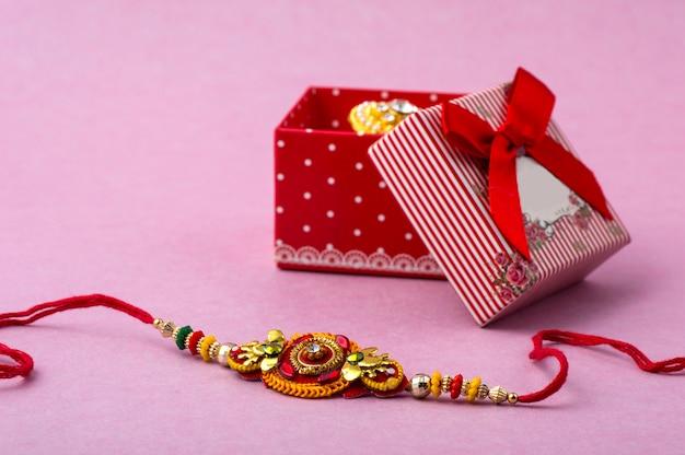 Raakhi et un cadeau pour la sœur offert par son frère à l'occasion de raksha bandhan. festival indien raksha bandhan avec un élégant rakhi.
