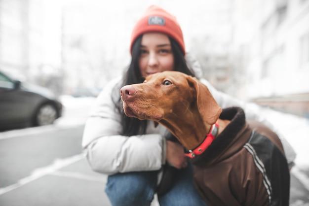 Race de chien magyar regarde sur le côté, mais la jeune fille souriante dans des vêtements chauds
