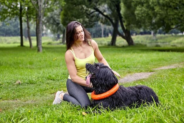 Race de chien noir briard allongé sur l'herbe et regarde sa propriétaire, qui est assise à proximité.